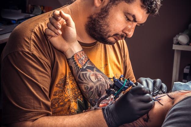 彫師はパーラーでタトゥーの写真を作ります
