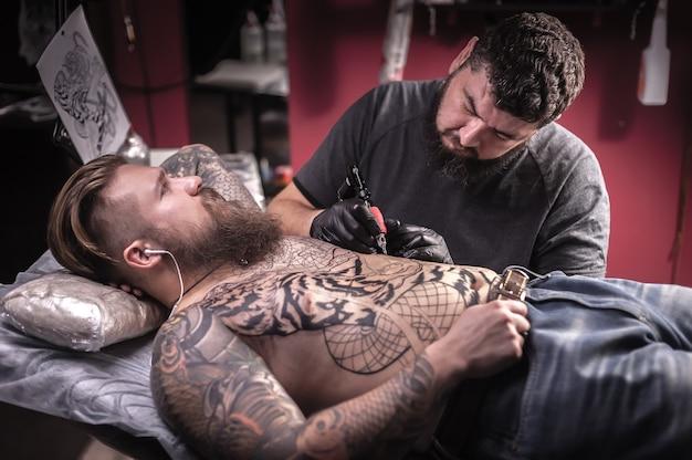 Татуировщик делает татуировки в тату студии.