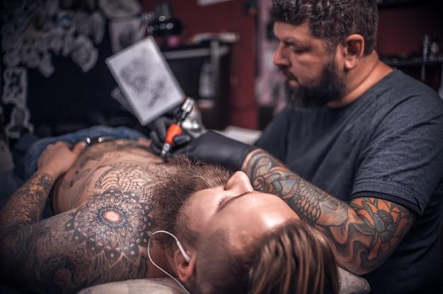 タトゥースタジオでタトゥーを作る彫師/ワークショップスタジオで働くマスター。