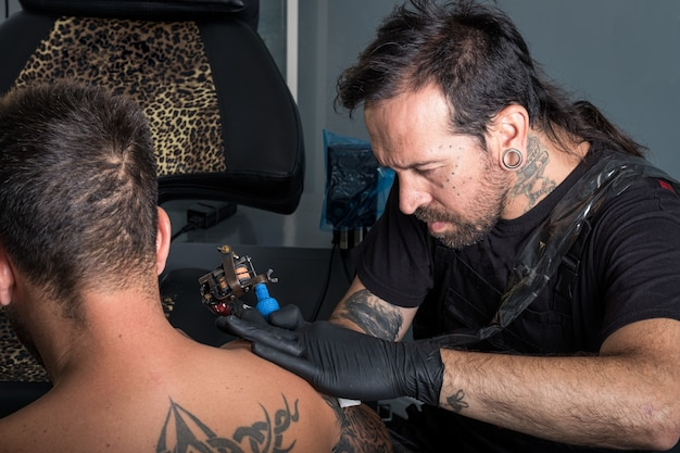 Tattooist making a tattoo on the arm of a client in a studio