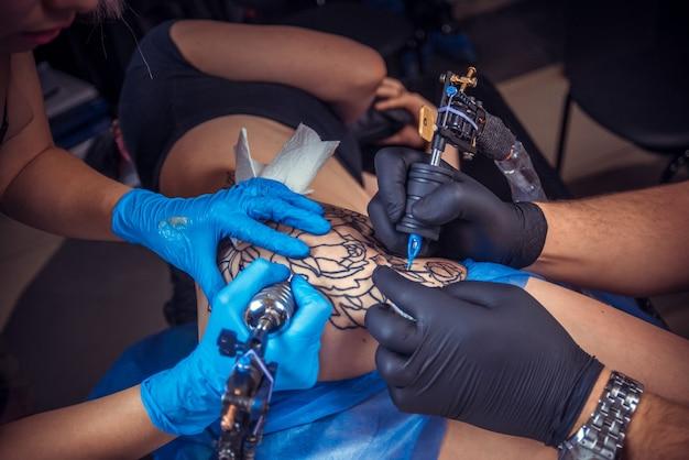 Татуировщик показывает татуировку краской в тату салоне