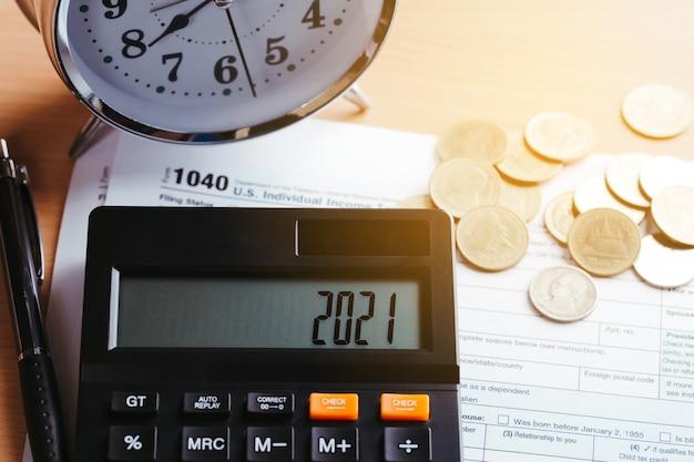 税2021ビジネスファイナンスの概念。テーブルにお金とフォーム1040の電卓。年間納税