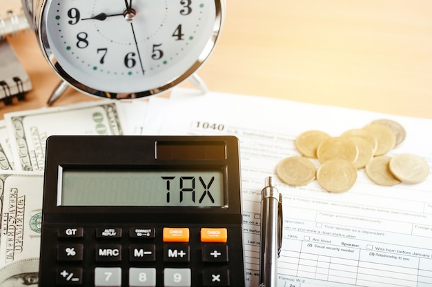 Tax 2021 business finance concept. calculator with money and form 1040 on table.annual tax payment