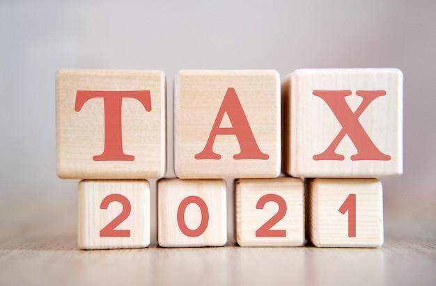 木製の立方体、木製の背景に2021年の税金。