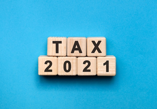 Tax2021-グラデーションの青い背景を持つ木製の立方体のテキストの概念。