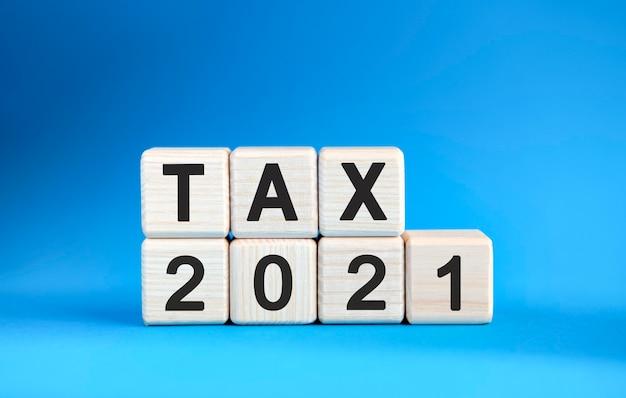 青い背景の上の木製の立方体の税2021年