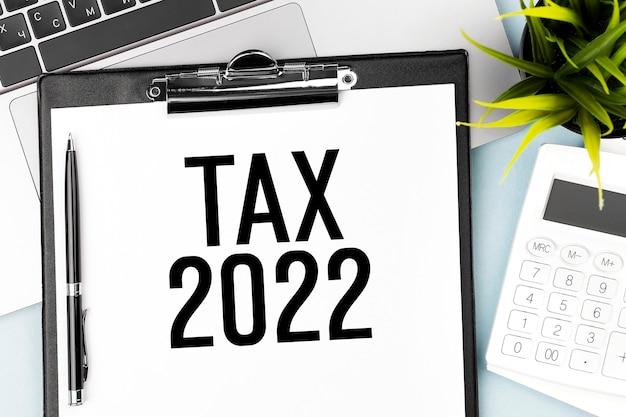 Tax2022。クリップボード、電卓、ラップトップ。会計の概念。フラットレイ。