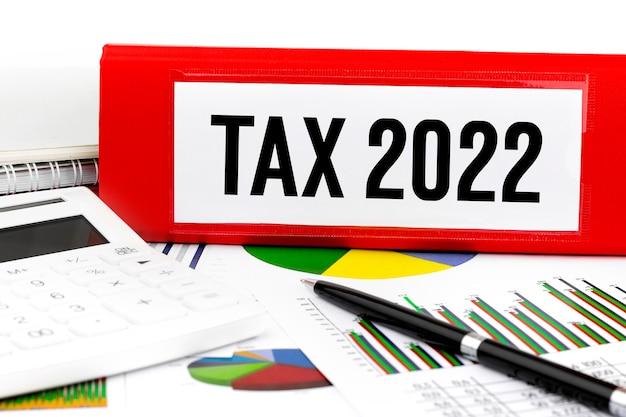 Tax2022。フォルダ、計算機、チャート。会計の概念。フラットレイ。