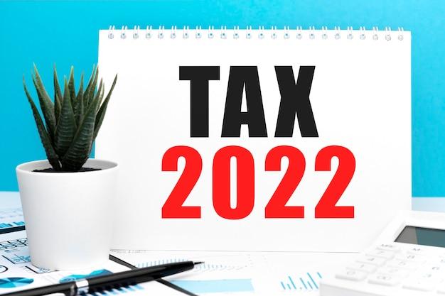 Tax2022。ノートブック、計算機、チャート。ビジネスコンセプト。フラットレイ。