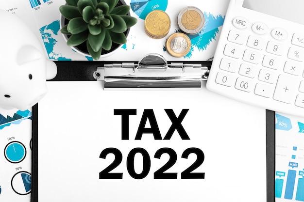 Tax2022。ピギー、コイン、電卓、チャート。ビジネスコンセプト。フラットレイ。