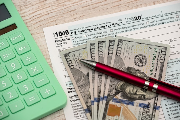 Tax and accounting concept, 1040 form pen calculator and dollar bills