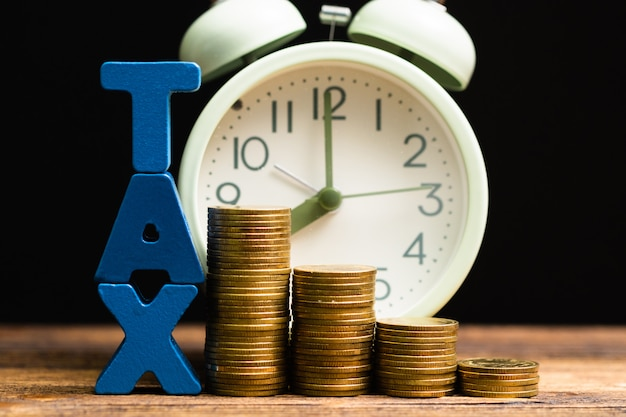 Tax alphabet with stack of coin and vintage alarm clock on wood