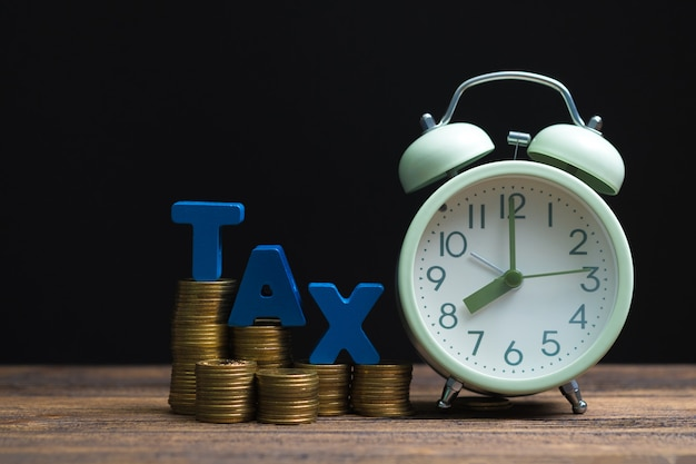 Tax alphabet with stack of coin and vintage alarm clock