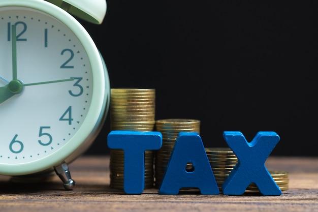 木の上のコインとビンテージの目覚まし時計のスタックで税のアルファベット