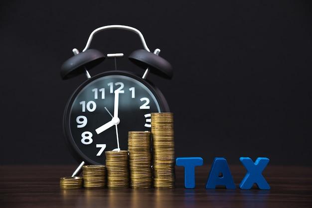 Налоговый алфавит со стопкой монет и винтажным будильником