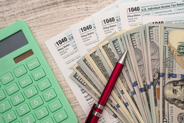 세금 및 회계 개념, 1040 양식 펜 계산기 및 달러 지폐