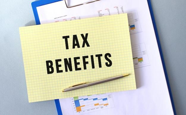 Налоговые преимущества текст, написанный на блокноте карандашом. блокнот на папке с диаграммами.