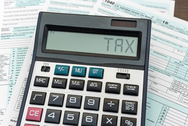 机の上の計算機と税の概念1040税フォーム。ファイナンスタイム