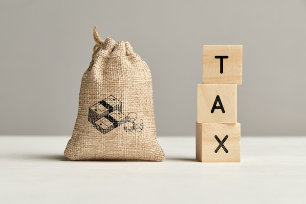Tax concept next to a bag of money. close up.