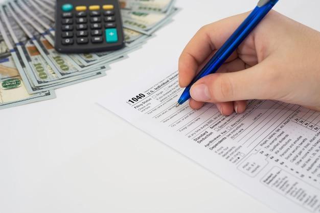 税の概念。米国の税務フォームを手で提出するクローズアップ。税務フォーム私たちビジネス収入オフィスハンドフィルの概念