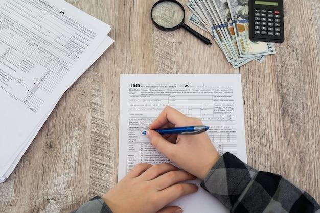 Налоговая концепция. крупным планом рука подачи налоговой формы сша. налоговая форма сша бизнес доход офис рука заполнить концепция