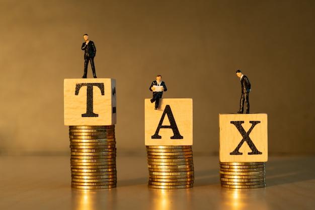税の概念。ミニチュアのビジネスマンおよび金貨。