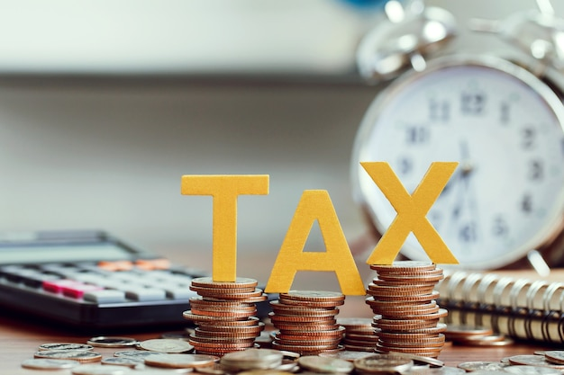 Tax concept. word tax put on coins and calculator, clock with coins on desks.tax time concept