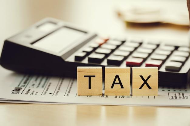 Налоговая концепция. слово налог на бумаге с калькулятором рассчитал индивидуальный подоходный налог для уплаты налогов
