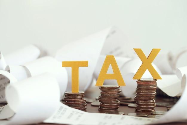 세금 개념입니다. 나무 테이블에 쌓인 동전과 지폐에 단어 세금. 세금 시간