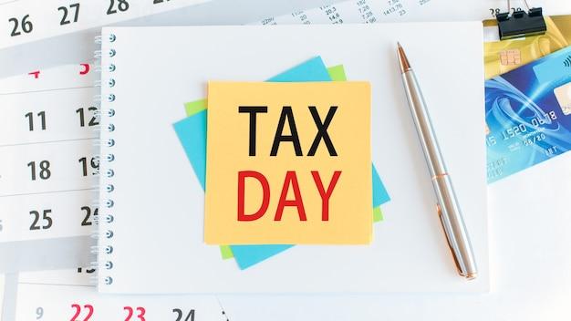 黄色い紙の正方形に書かれた税の日が追加されました。白いデスクトップ上のクレジットカード、ペン、文房具。ビジネス、金融、教育の概念。セレクティブフォーカス。