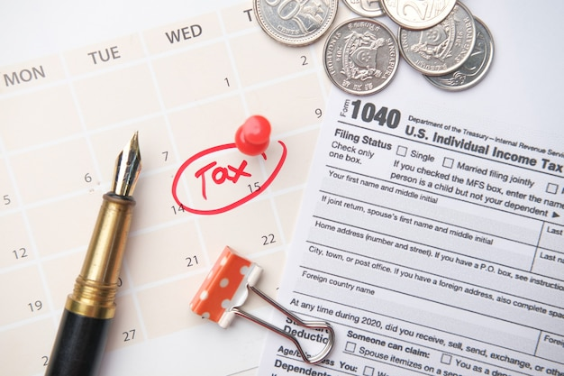 Tax day concept with red circle on calendar date and tax return on table