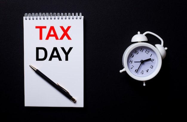 Tax day is written in a white notepad near a white alarm clock on a black surface.