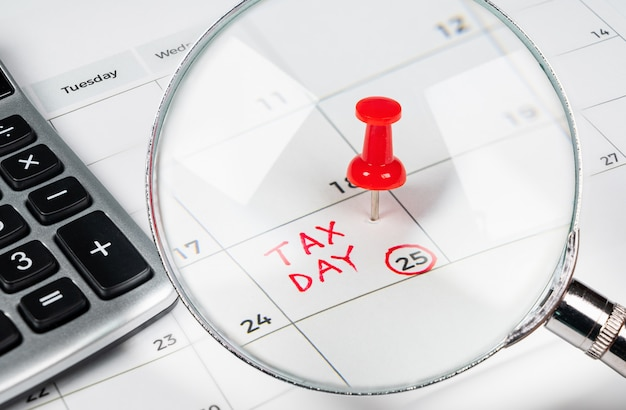 Tax day written on a calendar with a red pushpin.