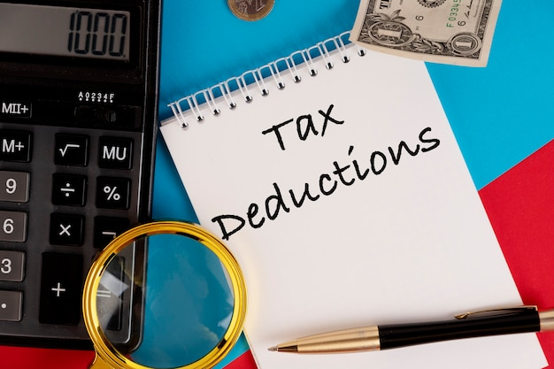 Tax deductions, the text is written in a white notepad, next to a calculator, a pen and a magnifying glass.