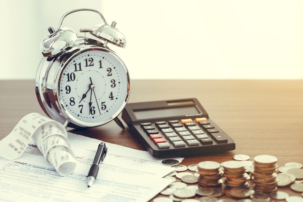 Tax-filling concept .tax form 1040 with pen, clock,coins and calculator on desk.tax concept