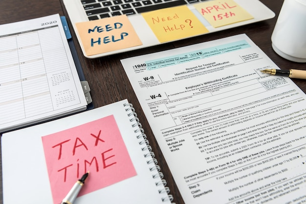Tax financial forms with pen and  calculator and sticker with text tax time. deadline, paperwork