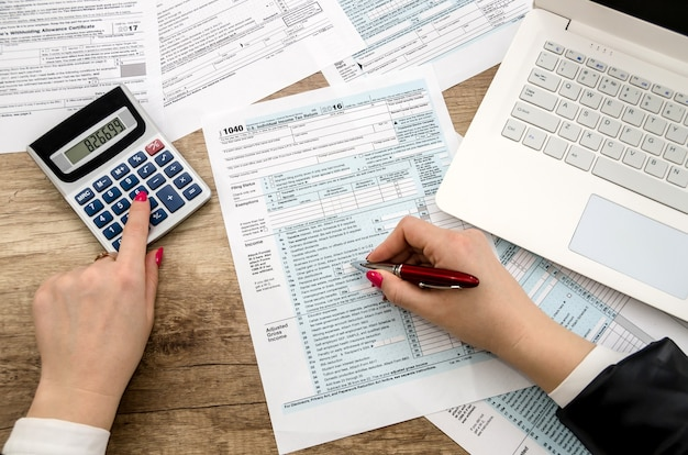 Tax form 1040 human hands and laptop
