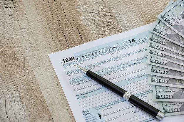Tax form 1040 with dollars and a pen on the table