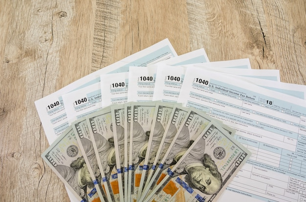 Tax form 1040 with dollars  on the table