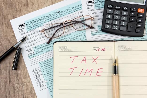 メモ帳とテキストの納税時間、ペン、電卓を備えた納税フォーム1040。税の概念