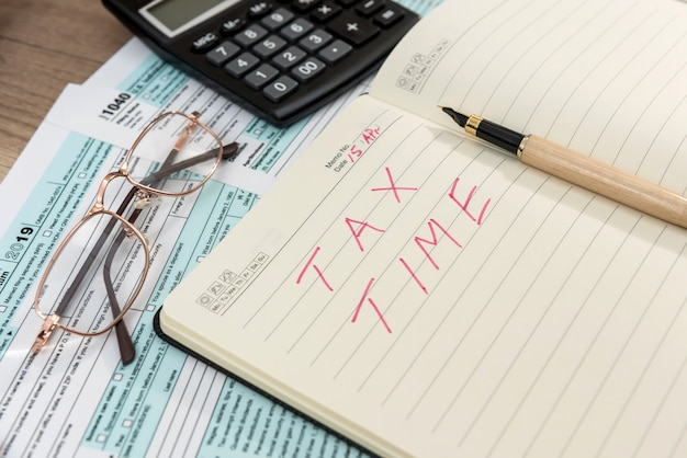 Tax form 1040 with notepad and text tax time, pen and calculator