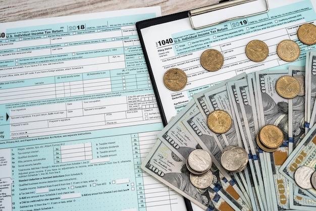 私たちと一緒に税金フォーム1040ドルとコイン計算機。ビジネスと税の概念。 20192020年に税金を支払う。