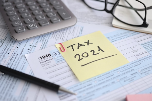 Tax form for  and calculator with pen are on t table