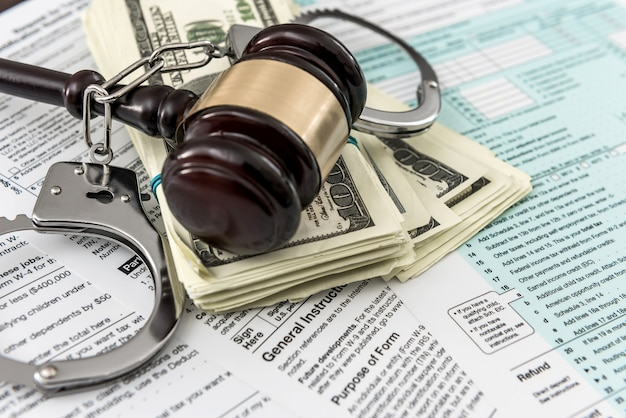 Tax form concept us money with handcuffs gavel lying on federal tax