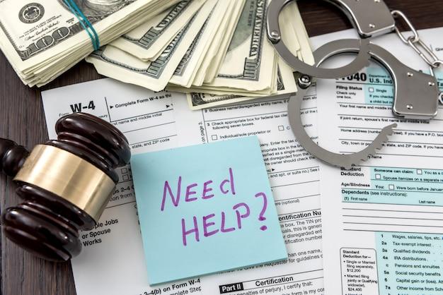納税申告書のコンセプトは、連邦税の上に横たわる手錠の小槌でお金を手に入れる