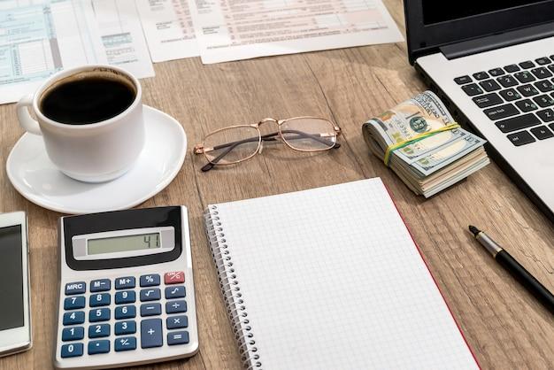 세금 양식, 노트북, 커피 및 책상에 달러