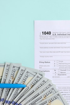 Tax form lies near hundred dollar bills and blue pen