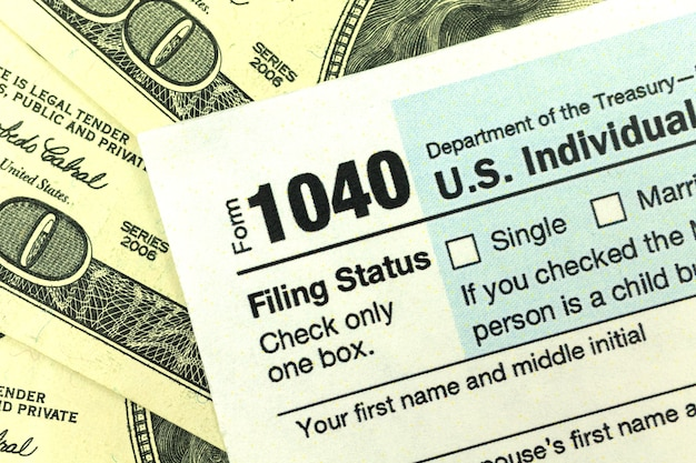 Tax form lying on us dollar bills close-up background