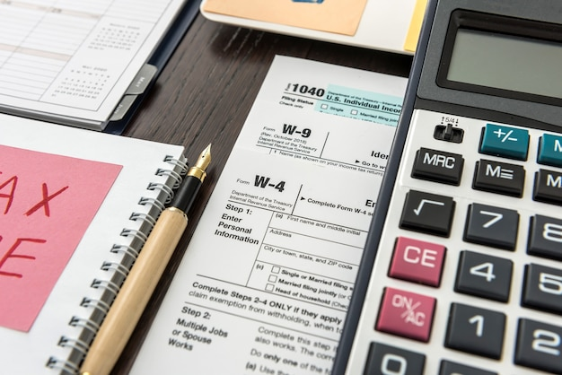Tax form, pen and calculator at office desk