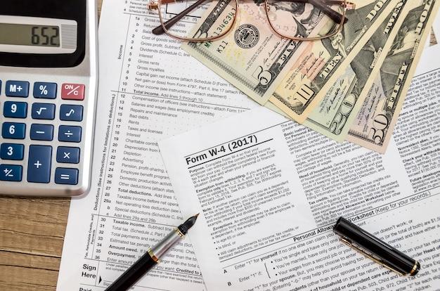 ドル、ペン、電卓付きの納税申告書w4